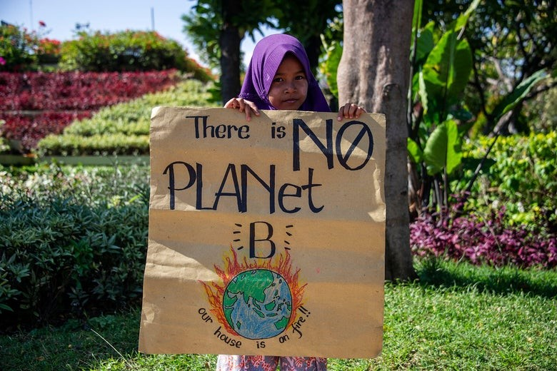 "An Indonesian child holds a placard that says ""there is no planet b."""